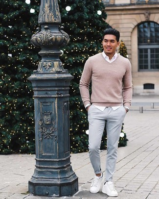 White Leather Low Top Sneakers Outfits For Men: Inject new life into your day-to-day casual repertoire with a beige v-neck sweater and grey chinos. Finish this ensemble with a pair of white leather low top sneakers to switch things up.