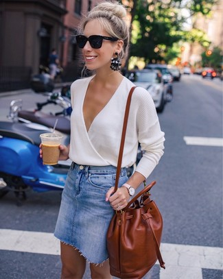 How to wear: beige v-neck sweater, blue denim mini skirt, tobacco leather backpack, black sunglasses