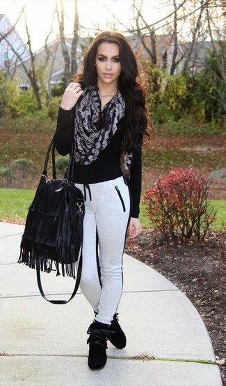 How to wear: black v-neck sweater, white and black sweatpants, black suede high top sneakers, black fringe leather tote bag