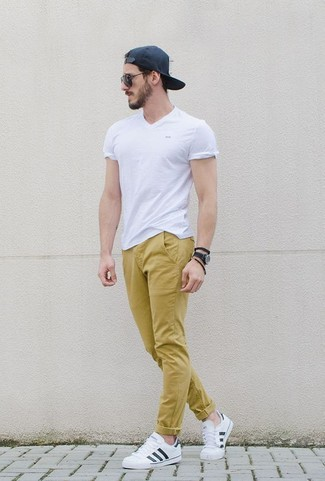 How to wear: white v-neck t-shirt, mustard chinos, white leather low top sneakers, black baseball cap
