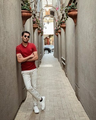 Grey Chinos Outfits: Effortlessly blurring the line between cool and off-duty, this pairing of a red v-neck t-shirt and grey chinos will likely become your favorite. If you don't know how to round off, a pair of white leather low top sneakers is a surefire option.