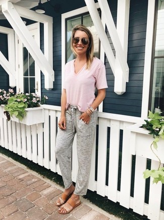 How to wear: pink horizontal striped v-neck t-shirt, grey sweatpants, tan leather flat sandals, dark brown sunglasses