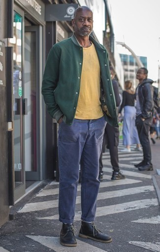 How to Wear Black Leather Desert Boots: A dark green varsity jacket and navy chinos are wonderful menswear essentials that will integrate brilliantly within your current casual arsenal. Finishing with a pair of black leather desert boots is an effective way to introduce a bit of flair to this look.