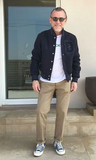 Varsity Jacket Outfits For Men: Go for a simple but casual and cool option teaming a varsity jacket and khaki chinos. Bring a fun feel to this look by rounding off with a pair of blue canvas high top sneakers.