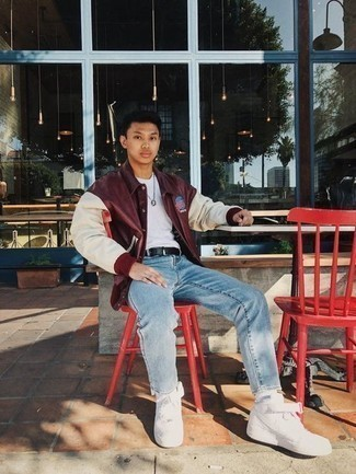 Men's Outfits 2020: A burgundy varsity jacket and light blue jeans are the perfect foundation for a casually dapper look. White canvas low top sneakers will pull the whole thing together.