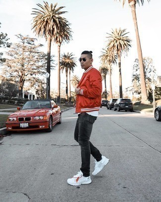 White Athletic Shoes Outfits For Men: This relaxed combo of a red varsity jacket and charcoal ripped jeans can go different ways depending on the way you style it. A pair of white athletic shoes can integrate brilliantly within a variety of outfits.