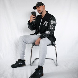 Black Print Varsity Jacket Outfits For Men: For a relaxed casual look with an urban twist, try pairing a black print varsity jacket with grey sweatpants. A great pair of black print leather low top sneakers is the simplest way to add a confident kick to the ensemble.