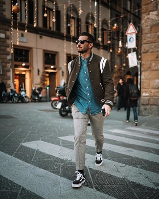 How to wear: black and white varsity jacket, blue denim shirt, grey wool chinos, black and white canvas low top sneakers