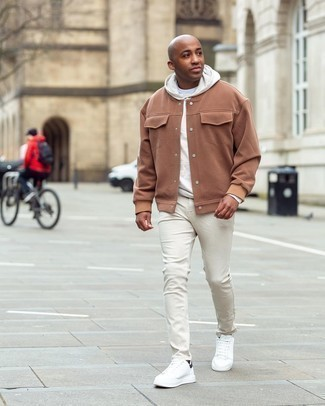White Jeans Outfits For Men: This pairing of a tan varsity jacket and white jeans is a safe go-to for a devastatingly stylish look. A great pair of white and black leather low top sneakers ties this outfit together.