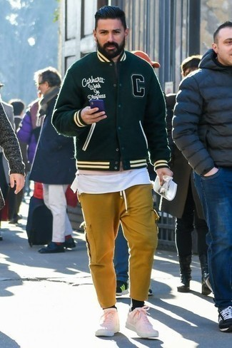 How to Wear a Sweater For Men: Who said you can't make a stylish statement with a casual outfit? You can do so with ease in a sweater and mustard cargo pants. Introduce a pair of pink leather low top sneakers to your ensemble to avoid looking too casual.
