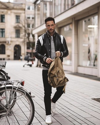 How To Wear Black Jeans With White Low Top Sneakers For Men: Display your credentials in men's fashion by wearing this off-duty combo of a black and white leather varsity jacket and black jeans. The whole look comes together if you add a pair of white low top sneakers to the mix.