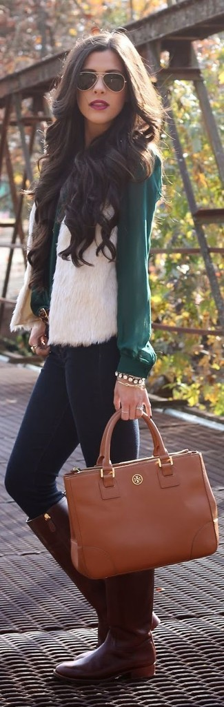 A white fur vest and navy skinny jeans feel perfectly suited for weekend activities of all kinds. Why not introduce dark brown leather knee high boots to the mix for an added touch of style?