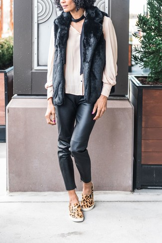 How to wear: black fur vest, beige button down blouse, black leather skinny pants, tan leopard slip-on sneakers