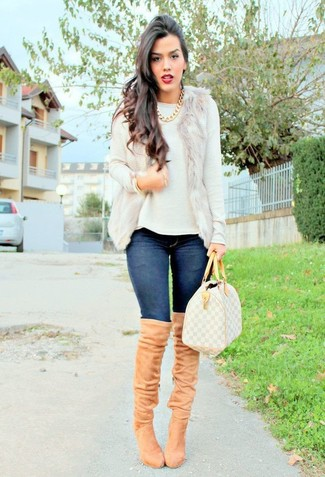 Let everyone know that you know a thing or two about style in a beige fur vest and navy blue slim jeans. To add oomph to your look, finish off with khaki suede over the knee boots. Keep this outfit in your front hall closet when spring sets it, and we promise you'll save time planning what to wear on more than one morning.