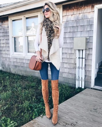 How to Wear Tan Suede Over The Knee Boots: If you're looking for a laid-back and at the same time incredibly chic outfit, dress in a beige fur vest and blue skinny jeans. For shoes, you can go down a more elegant route with a pair of tan suede over the knee boots.