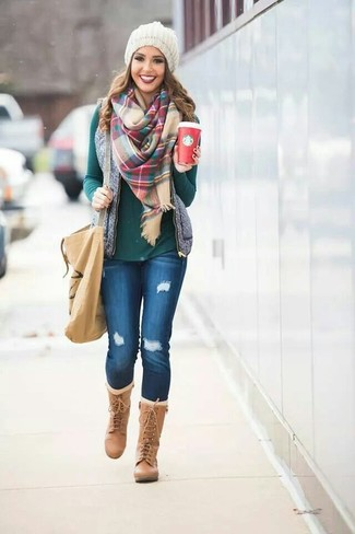 A grey quilted vest and blue destroyed slim jeans feel perfectly suited for weekend activities of all kinds. Rock a pair of tan leather knee high boots to va-va-voom your outfit.