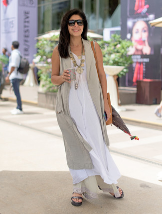 Opt for comfort in a beige vest and a white linen maxi dress. Make black leather flat sandals your footwear choice to have some fun with things. This here is hard proof that it is indeed possible survive the summer heat and look easy breezy while doing so.