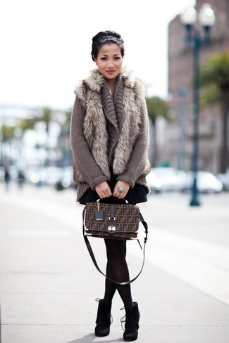 Try pairing a grey fur vest with a black pleated skirt for a casual coffee run. Black suede booties will bring a classic aesthetic to the ensemble.