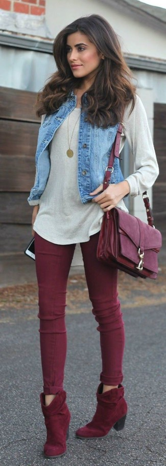 A blue denim vest and oxblood skinny jeans will give off this very sexy and chic vibe. Dress up this look with red suede booties.