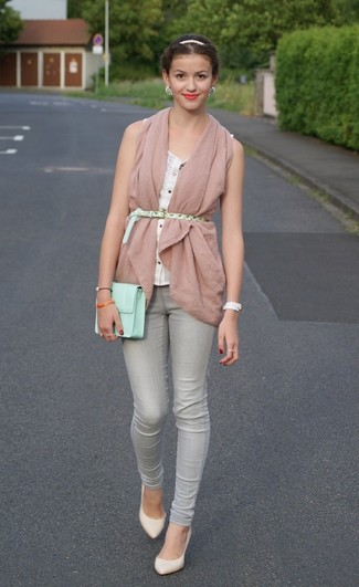 Reach for a pale pink vest and grey skinny jeans for a glam and trendy getup. A cool pair of white leather pumps is an easy way to upgrade your look.