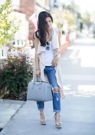 How to Wear Blue Ripped Boyfriend Jeans: This laid-back pairing of a beige vest and blue ripped boyfriend jeans is super easy to throw together in next to no time, helping you look awesome and prepared for anything without spending too much time combing through your wardrobe. Complement your look with a pair of beige leather wedge sandals to instantly shake up the look.