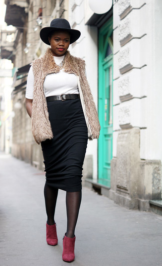 Pairing a camel fur vest with a black midi skirt is a comfortable option for running errands in the city. Make red suede ankle boots your footwear choice to va-va-voom your outfit.