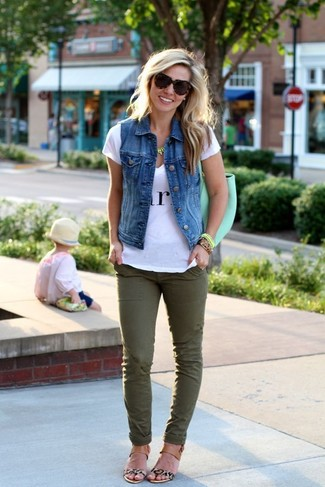 To create an outfit for lunch with friends at the weekend pair a blue denim vest with hunter green slim jeans. Dress down your look with beige leopard leather flat sandals.