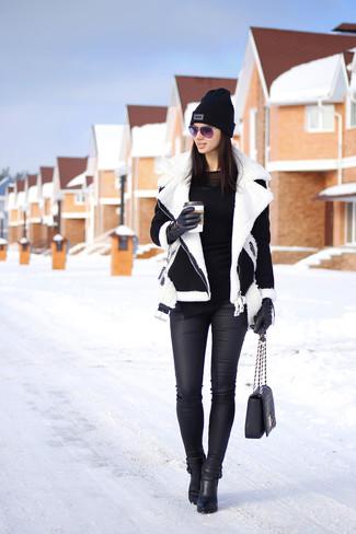 Tenue: Veste en peau de mouton retournée noire et blanche, T-shirt à manche longue noir, Jean skinny en cuir noir, Bottines en cuir noires