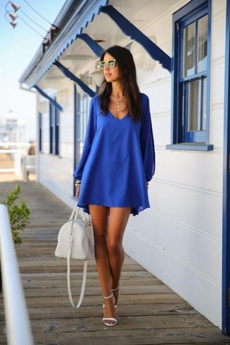 Cómo combinar: vestido amplio azul, sandalias de tacón de cuero blancas, bolso deportivo de cuero blanco, gafas de sol amarillas
