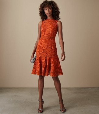 Cómo combinar: vestido de vuelo de encaje naranja, sandalias de tacón de cuero plateadas, cartera sobre con adornos plateada