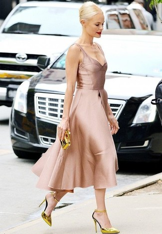 Cómo combinar: vestido de vuelo de satén rosado, zapatos de tacón de cuero dorados, cartera sobre dorada