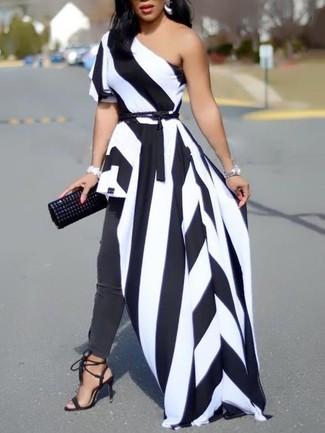 Cómo combinar: vestido largo de rayas verticales en blanco y negro, vaqueros pitillo en gris oscuro, sandalias de tacón de ante negras, cartera sobre de cuero con tachuelas negra