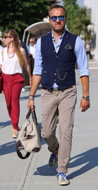 How to wear: navy waistcoat, light blue chambray long sleeve shirt, beige chinos, beige suede low top sneakers