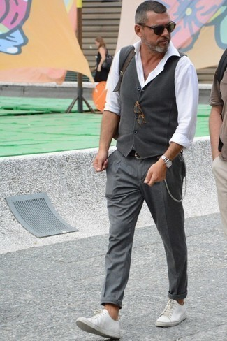 How to Wear a Belt After 40 For Men: This off-duty combo of a grey waistcoat and a belt is a safe option when you need to look sharp in a flash. If in doubt as to what to wear on the footwear front, add white leather low top sneakers to the mix.