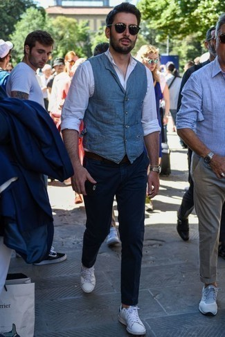 How to Wear White Leather Low Top Sneakers In Warm Weather For Men: This polished pairing of a blue waistcoat and navy chinos will prove your styling prowess. White leather low top sneakers will give a more laid-back finish to an otherwise dressy look.