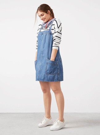 Wear a white and black horizontal striped crew-neck sweater and a blue denim overall dress to get a laid-back yet stylish look. A pair of white low top sneakers looks very fitting here. With spring coming, it's time to make space for simple and stylish looks, just like this one.
