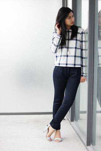 If you're a fan of classic pairings, then you'll like this combination of a white and black crew-neck jumper and navy fitted pants. Elevate this ensemble with light blue leather heeled sandals.