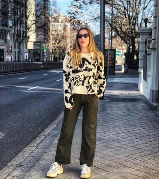 How to Wear White Athletic Shoes For Women: A white and black tie-dye crew-neck sweater and olive tie-dye denim wide leg pants make for the ultimate chic casual look. A pair of white athletic shoes effortlesslly revs up the appeal of this ensemble.