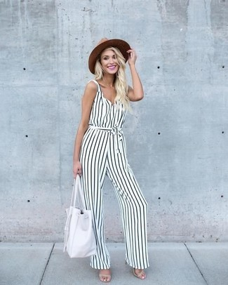 How to wear: white and black vertical striped jumpsuit, beige leather heeled sandals, white leather tote bag, brown straw hat