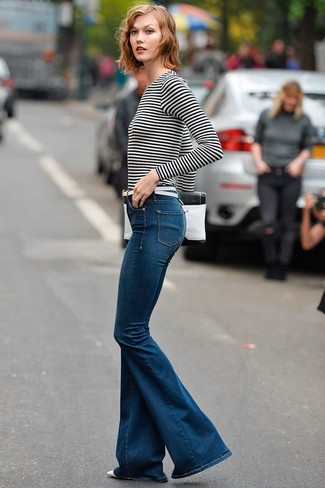 Karlie Kloss wearing White and Black Horizontal Striped Long Sleeve T-shirt, Navy Flare Jeans, White and Black Leather Clutch, White Leather Belt