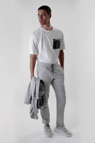 How to Wear a Track Suit For Men: A track suit and a white and black print crew-neck t-shirt are a good look to keep in your casual styling rotation. Let your sartorial expertise really shine by finishing off this ensemble with grey athletic shoes.