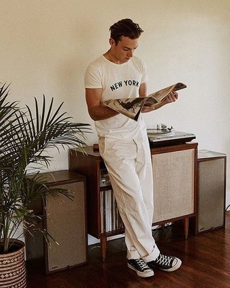 How to Wear Black and White Canvas Low Top Sneakers For Men: Infuse style into your day-to-day off-duty rotation with a white and black print crew-neck t-shirt and white chinos. Black and white canvas low top sneakers will pull this whole ensemble together.