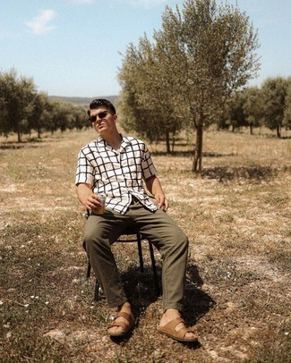 17 Relaxed Outfits For Men: Choose a white and black check short sleeve shirt and olive chinos for a casually stylish and trendy outfit. Brown leather sandals can effortlessly dial down an all-too-refined outfit.