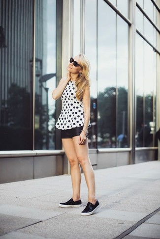A white and black polka dot sleeveless top and black leather shorts are perfect for both running errands and a night out. Why not add black leather slip-on sneakers to the mix for a more relaxed feel?