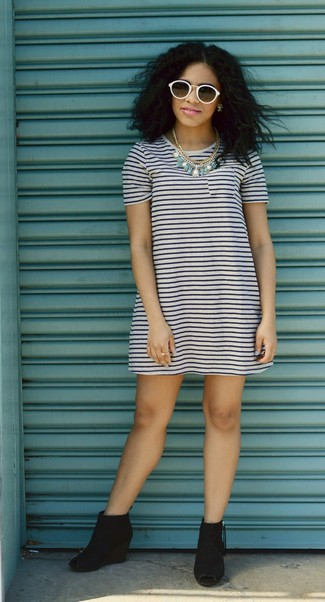 Dress in a white and navy striped casual dress for a casual coffee run. Grab a pair of black cutout suede wedge ankle boots to va-va-voom your outfit.