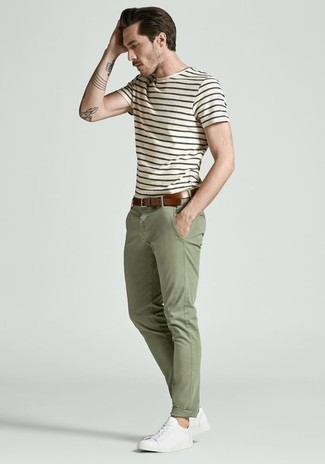 Olive Chinos Casual Outfits: Extremely dapper, this laid-back combination of a white and navy horizontal striped crew-neck t-shirt and olive chinos provides with excellent styling opportunities. White canvas low top sneakers look right at home here.
