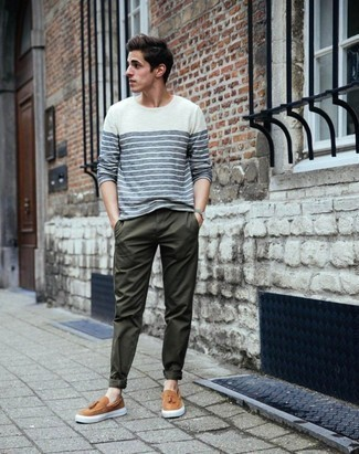 How to Wear Dark Green Chinos: The pairing of a white and navy horizontal striped long sleeve t-shirt and dark green chinos makes this a solid relaxed casual outfit. Take your ensemble in a more elegant direction by finishing with tan leather slip-on sneakers.