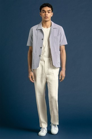 Men's Outfits 2021: Stand out among other dudes in a white and navy vertical striped short sleeve shirt and white chinos. A pair of white leather low top sneakers looks perfect here.