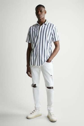 White and Navy Vertical Striped Short Sleeve Shirt Outfits For Men: For a cool and relaxed ensemble, try teaming a white and navy vertical striped short sleeve shirt with white ripped jeans — these two pieces work beautifully together. Finishing with a pair of white leather low top sneakers is an effective way to bring a dose of refinement to this outfit.