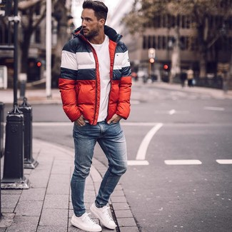 How to wear: white and red and navy puffer jacket, white crew-neck t-shirt, blue skinny jeans, white leather low top sneakers